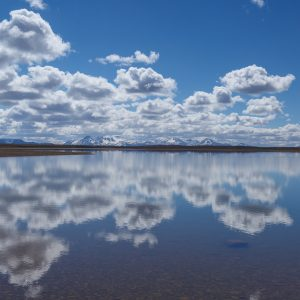 Blue sky with clouds reflecting in the water